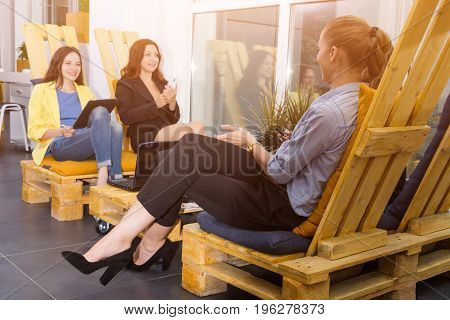 Group of pretty businesswomen working together with new startup project using laptop computer in modern loft. People and teamwork concept - happy creative team in office. Casually dressed female colleagues talking in a meeting room.