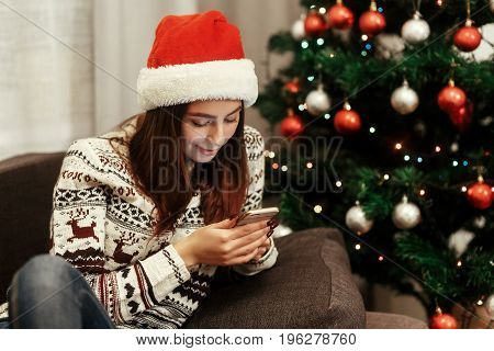 Smiling, Beautiful Brunette Woman In Red Santa Claus Hat And White Reindeer Sweater Browsing On Her