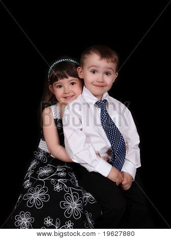 Adorable Portrait Of Brother And Sister Sitting. Isolated On Black