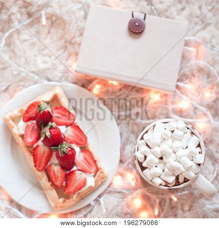 Cup of coffee with marshmallows strawberry waffle and note book on fluffy background. Good morning. Breakfast. Top view. Selective focus.