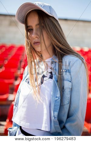 Portrait of beautiful stylish young woman in blue shirt with red plastic chairs on background on stadium