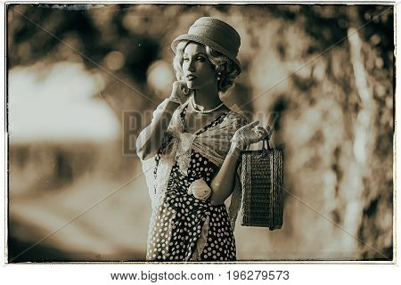 Classic black and white photo of 1930s fashion woman standing with handbag on rural pathway. poster
