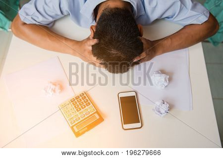 Businessmen to put his hand to the head , stressed because they have to work hard at office desk.