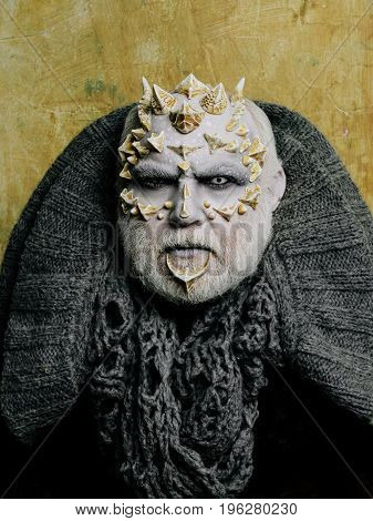 Monster face with white eyes sharp thorns and warts. Alien or sorcerer makeup. Demon head with grey collar on abstract beige wall. Horror and fantasy concept. Man with dragon skin and beard.