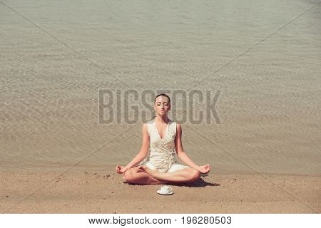 Woman Meditating In Yoga Pose With Coffee Cup At Water