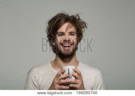 smiling man with cup of tea or coffee has uncombed hair in underwear on grey background morning refreshment and drink