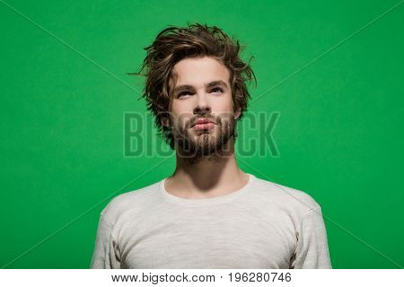 morning wake up of concentrated man with beard and long hair in white underwear on green background barbershop