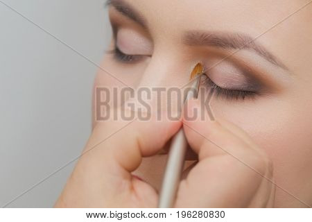 Hand With Brush Applying Shadows On Woman Face