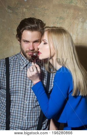 Macho and woman posing with glass of red liqueur. Cute girl with blond long hair and handsome man on beige background. Couple in love. Alcohol and appetizer. Unhealthy lifestyle and bad habits