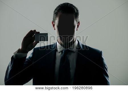 Faceless man in formal suit and tie on grey background. Shadow business and economy banking fraud skimming ecash and information