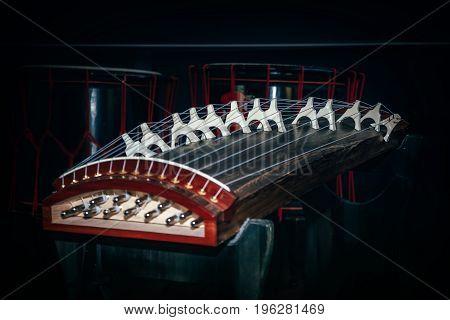 Musical String Instrument of easr asia koto yatga guzheng chinese zither zheng gayageum om dark background. Selective focus on picture.