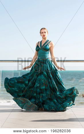 Fashion outdoor photo of a gorgeous woman in a luxurious green silk dress, posing near a bright blue sea. Young beautiful lady in a long dress on the terrace of a luxury hotel.