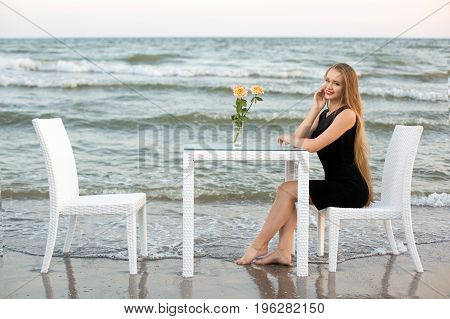A lady sitting next to the white table on a vacation. A charming girl posing on a light blue sea background. A female with long hair and a sturated black dress. Blooming peachy roses in a glass.