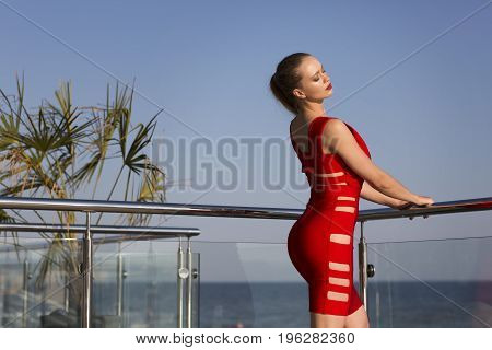 A stunning young woman in a bright red dress relaxing on a hotel terrace on a natural blue background. A tall girl with a perfect posture next to the green palms on a summer holiday.