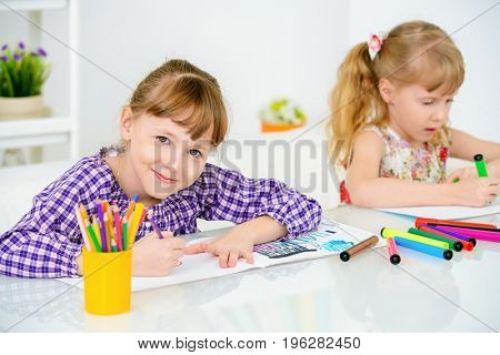 Happy girls sisters draw at home. Free time, activity and hobby. Education.