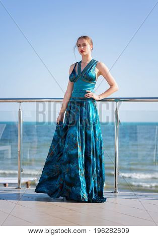 A fashionable and elegant girl in a turquoise dress on a bright blue sea background. A glamorous and young lady is staying on a glass balcony on a blue sky background. A stylish woman near the sea.