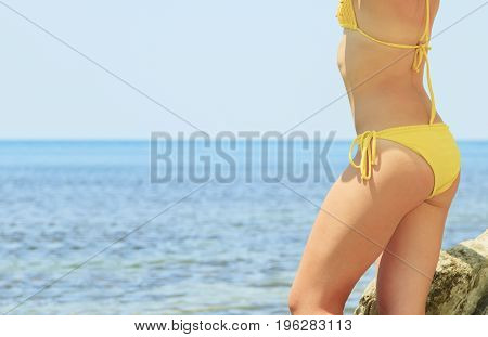 Rear view of the female booty over blue sea