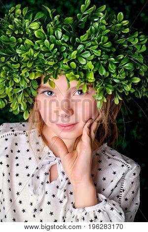 Portrait of a beautiful summer girl wearing green wreath in a green summer garden. Children's fashion.