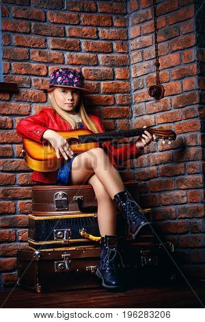 Modern child girl playing guitar and singing a song. Rock star, rock music, pop music concept.