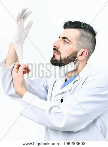 Surgeon With Beard In Laboratory Coat Puts Glove On