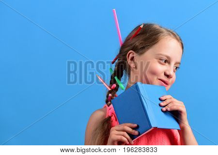 Girl Holds Blue Book And Smiles. Kid In Pink Blouse