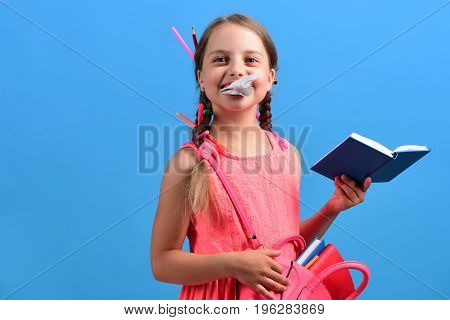 Back To School And Education Concept. Girl Eats Paper