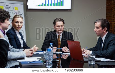 Group of serious people sitting at table and having discussion.