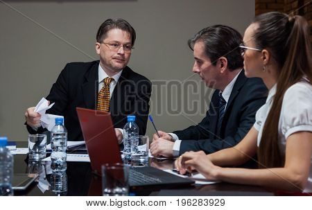 Male boss sitting at table with office workers and looking displeased.
