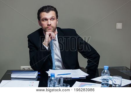 Young male in suit sitting at table and looking away.