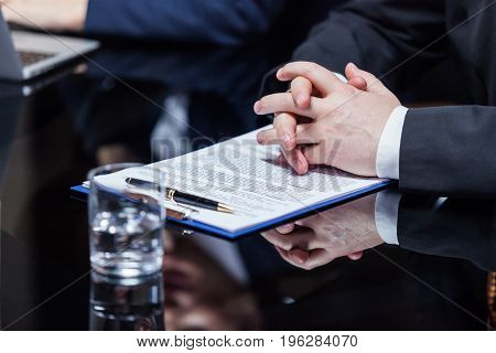 Horizontal crop shot of a businessman sitting and holding hands on documents during the meeting.
