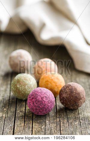Sweet truffle balls on wooden table.