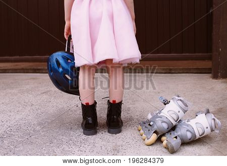 Inline skates sport conceptual image. Active outdoor sport for kids. Young girl is holding a helmet for roller skating in a pink fluffy skirt, at the feet lie roller skates.