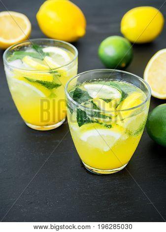 Fresh citrus cold lemonade with limes and lemons in glasses