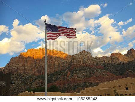 USA flag in landscape with mountains and blue sky