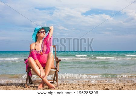Woman sitting on a deck chair at the beach in Greece