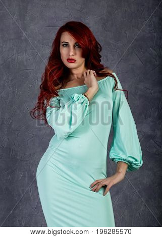Portrait of beautiful redhead young woman with big boobs in a turquoise dress on a gray background.