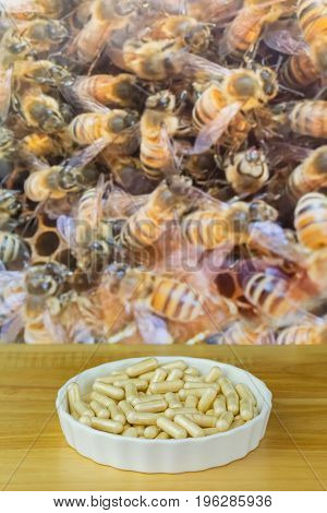 Bowl of Royal Jelly in capsules with blurred background of worker bees working in honeycomb, premium bee products used as dietary supplement
