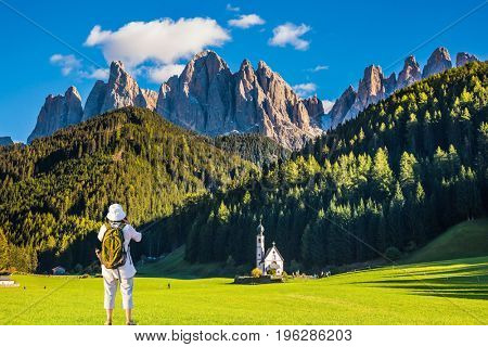 Dolomites, Tirol. Active woman-tourist with backpack photographs the church of Santa Maddalena. Forested mountains surrounded by green Alpine meadows. The concept of ecological and active tourism
