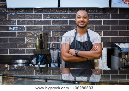 Portrait of a smiling african waiter standing in the cafeteria with crossed arms. Confident young man with apron in coffee shop looking at camera. Handsome black guy working in a coffeeshop.