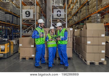 Two male and female workers wearing protective uniform standing in front of packages looking at clipboard.