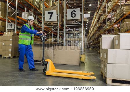 Male worker wearing blue uniform jacket and hardhat driving pallet truck towards pallets with boxes.