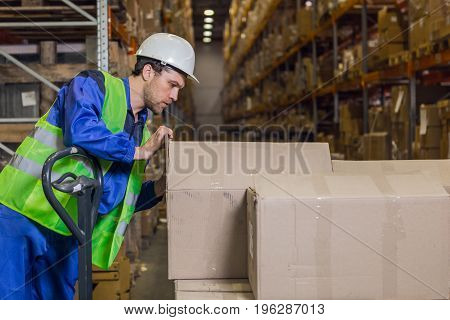 Storehouse worker checking boxes with merchandise in warehouse