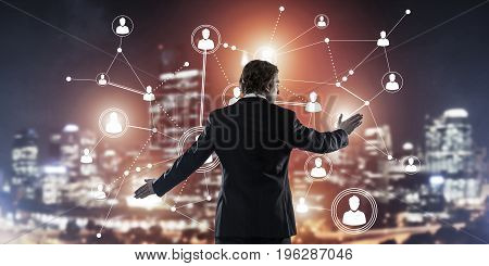 Back view of businessman against night cityscape working with social connection media concept