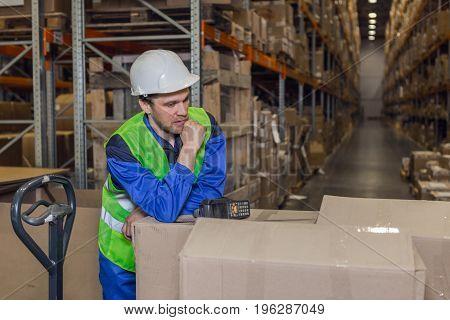 Man wearing blue uniform yellow jacket white hardhat leaning upon cardboard boxes standing in warehouse.