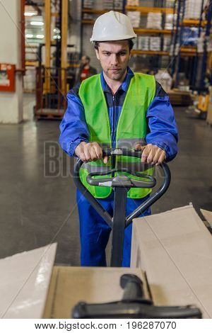 Man with stubble wearing uniform and hardhat steering pallet truck carrying boxes in warehouse.