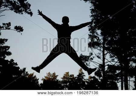Silhouette Jumping Man Against Blue Sky.