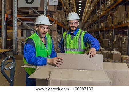 Male workers looking inside boxes in warehouse