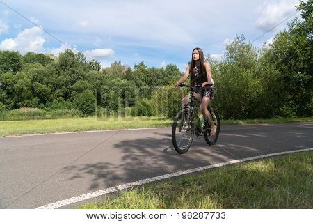 Girl riding a bicycle. Side view. Forest and clouds in the background.
