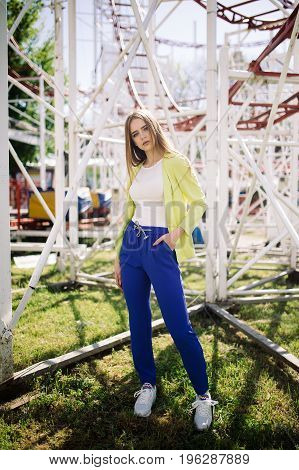 Portrait of beautiful stylish young woman in blue trousers standing in amusement park