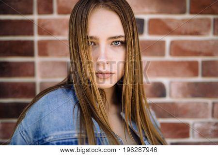 Portrait of beautiful stylish young woman posing against brick wall